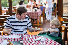 Young father and son having breakfast together in summer Stock Image