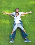 Young father and son lying on a meadow together. In the park stock photos