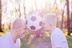 Young father and son playing with ball on green grass in park. Happy family in the park royalty free stock photos