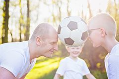 Young father and son playing with ball on green grass in park. Happy family in the park royalty free stock photography