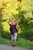 Young father with son on shoulders standing against a background of tropical green forest. Back view. Sunlight.  Stock Photo