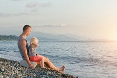 Young father and son are sitting on the beach against the backdrop of the sea and city  in the distance Royalty Free Stock Images