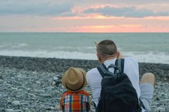 Young father and son are sitting on the beach against the backdrop of the sea and the setting sun.  Royalty Free Stock Photo