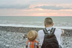 Young father and son are sitting on the beach against the backdrop of the sea and the setting sun.  Stock Photo
