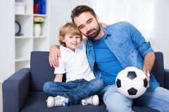 Young father and son sitting on sofa. With soccer ball Stock Photos