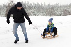 Young father and son sledding at winter time. Young father and son sledding wooden sledge at winter time Royalty Free Stock Photography
