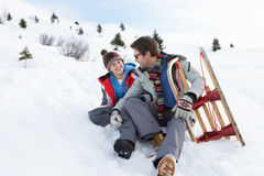 Young Father And Son In Snow With Sled. Smiling at each other Stock Photo