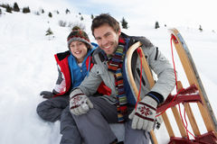 Young Father And Son In Snow With Sled. Smiling at camera Royalty Free Stock Images