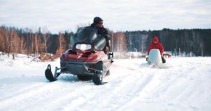 Young father and son on snowmobile stock footage