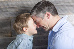 Young father with son in studio wood background. A Young father with son in studio wood background Royalty Free Stock Image