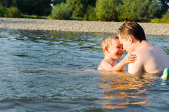 Young father and son swimming in river Royalty Free Stock Photo