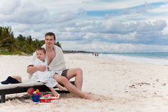 Young father and son on a tropical beach. Father and son wrapped in beach towels on a tropical beach Stock Image