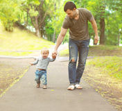 Young father and son walking in summer park Stock Images