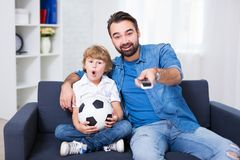 Young father and son watching football. On tv Royalty Free Stock Photography