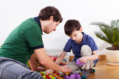 Young father spending time with son. Young caring father spending free time with son and playing Stock Photos
