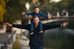 A young father is standing with his little son on his shoulders stock photos