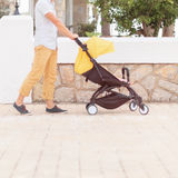Young father strolling pushchair with a baby. Closeup of young father strolling pushchair with sleeping baby Stock Images