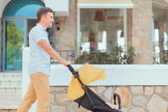 Young father strolling pushchair. With sleeping baby on city street Stock Image