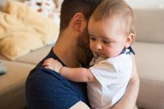 Father comforting crying baby. Young father taking care of crying baby Royalty Free Stock Photo