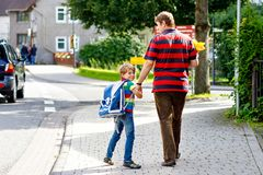 Young father taking child, kid boy to school on his first day. Parent taking child, kid boy to school. Pupil of primary school go study. Father holding hand of stock photos