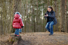 Young father taking a photo of his daughter Royalty Free Stock Image