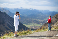 Young father taking picture of his son in mountains Royalty Free Stock Photo