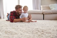 Young father taking selfie with toddler son in sitting room royalty free stock images