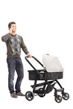 Young father talking on phone and pushing a baby stroller Royalty Free Stock Photo