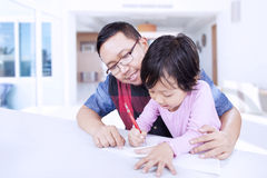Young father teaches a girl to write Stock Images