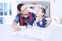 Young father teaches his son doing homework. Picture of a young father talking with his son while helping him doing homework at home royalty free stock photo