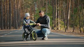 Young father teaches little son to ride a balance bike. Outdoors stock video