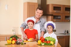 Young father teaching children how to prepare salad. Royalty Free Stock Photo