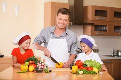 Young father teaching children how to prepare salad. Stock Photography