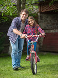 Young father teaching daughter how to ride a bicycle at park. Young father teaching his daughter how to ride a bicycle at park stock photography