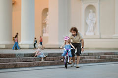Young father teaching his daughter to ride a bike Royalty Free Stock Photos