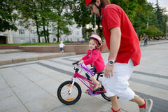 Young father teaching his daughter to ride a bike Royalty Free Stock Images
