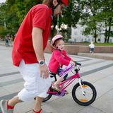 Young father teaching his daughter to ride a bike Stock Images