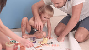 Young father teaching his kid boy how to paint Stock Images