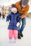 Young father teaching his little daughter to skate Stock Photo