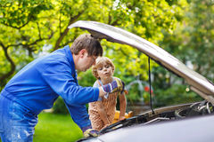 Young father teaching his little son to change motor oil in fami Royalty Free Stock Photography