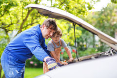 Young father teaching his little son to change motor oil in fami Royalty Free Stock Photos