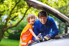 Young father teaching his little son to change motor oil in fami Stock Image