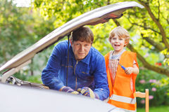 Young father teaching his little son to repair motor oil in fami Royalty Free Stock Photography