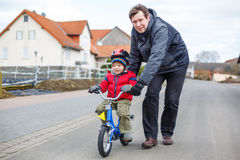 Young father teaching his 3 years old little son to ride a bike Royalty Free Stock Photo