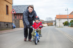 Young father teaching his 3 years old little son to ride a bike Stock Photography