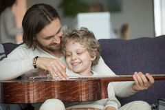 Young father teaching little son to play guitar at home royalty free stock image