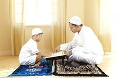 Young father teaching Quran to his son. Young father teaching Quran to his so while sitting on prayer carpet at home royalty free stock photography