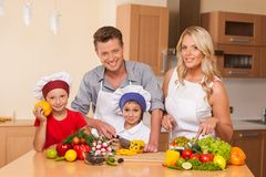 Young father teaching son how to prepare salad. Boy and girl helping with food at kitchen Stock Photo