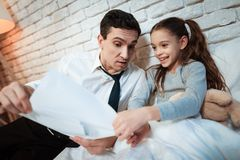 Young father tells his daughter about his work. Businessman shows little daughter than he does. stock images