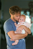 Young Father Tenderly Hugging Baby Daughter. A happy and peaceful young Christian father is lovingly holding and hugging his baby daughter at home stock photo
